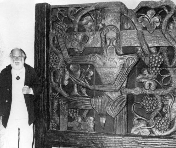 Lanza del Vasto posa delante de su escultura: el Cristo con vid